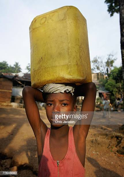 A young girl carries water back to her family from the river in Wilberforce November 26 2006 in Freetown Sierra Leone Sierra Leone was ravaged by a...