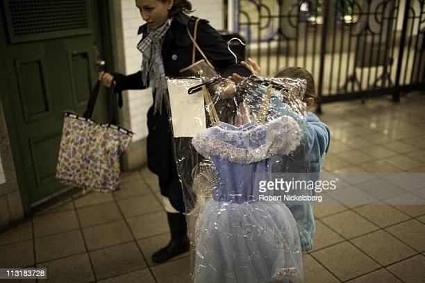 Young girl carrying a formal dress walks April 13, 2011 with her mother at a subway station in New York.