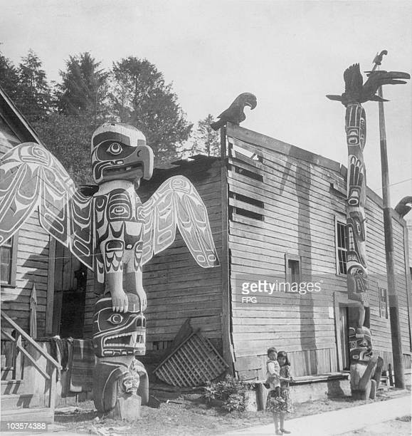 A young girl carrying a small child stands before Native American totem poles in British Columbia Canada circa 1950 Totem poles are sculptures carved...