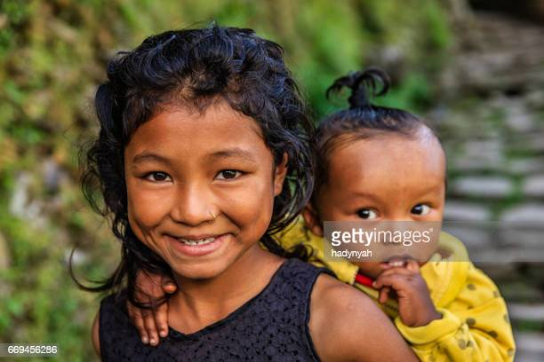 young girl carrying baby on the back, near annapurna range - annapurna conservation area stock photos and pictures