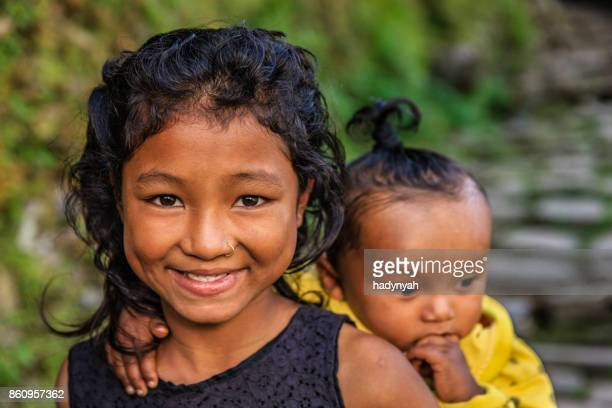 Young girl carrying baby on the back, near Annapurna Range