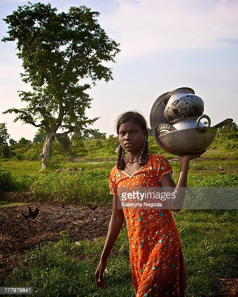Young girl carrying dishes which she washed in the nearby river in Raipur, India.