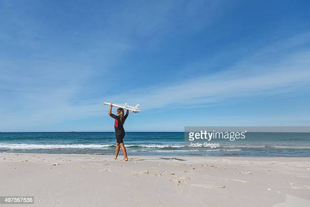 Young girl carrying surfboard above head walking towards the ocean