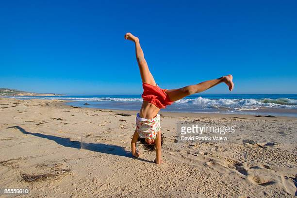 young girl cartwheels on the beach - cartwheel stock pictures, royalty-free photos & images