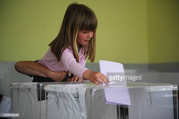 A young girl casts her mothers' vote at a polling station in Gracanica on May 6 2012 Serbians voted for a new president and parliament after a...