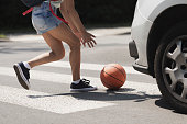 Young girl catching a basket ball on a pedestrian crossing