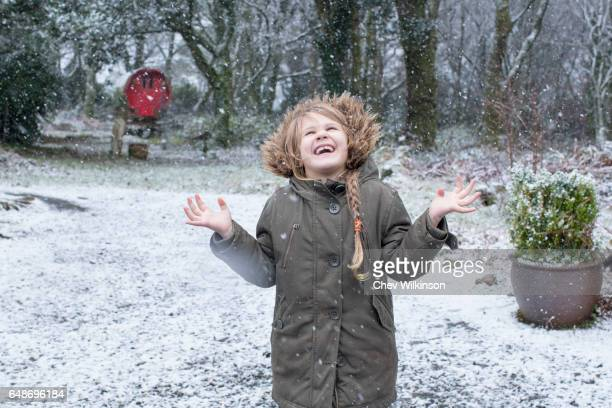 Young girl catching snowflakes