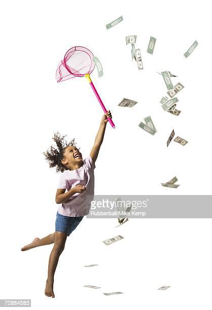 Young girl catching US banknotes with butterfly net