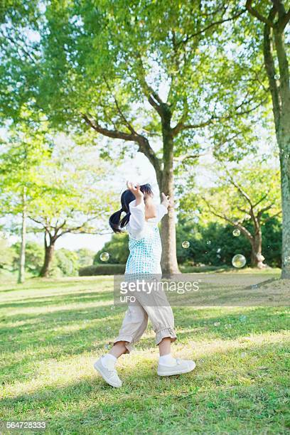 Young Girl Chasing Bubbles In Park