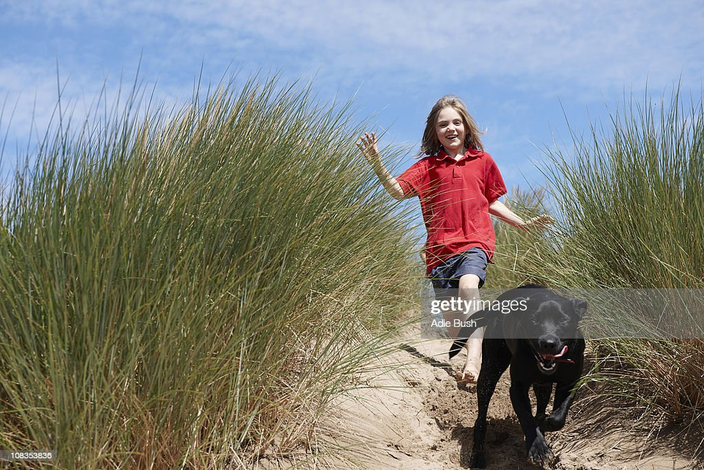 Young Girl Chasing dog in sand dunes : Stock Photo
