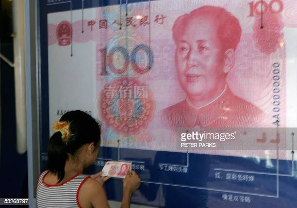 A young girl checks her 100 yuan note against a poster telling visitors how to spot a fake note at a Yuan exhibition at the Beijing Science Museum 22...