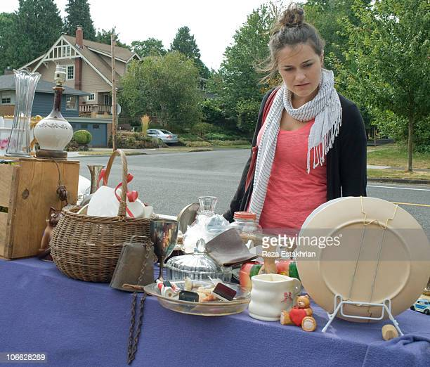 young girl checks products at yard sale - garage sale stock pictures, royalty-free photos & images