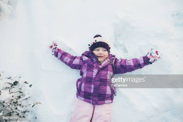 Young girl cheerfully doing a snow angel in the snow