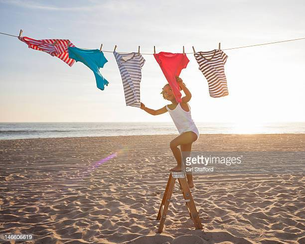 a young girl choosing a t-shirt from a clothesline - black slip photos et images de collection