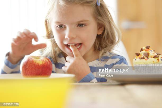 young girl choosing an apple over a cake - temptation stock pictures, royalty-free photos & images