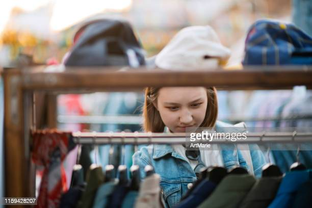 young girl choosing clothes in a second hand market in summer, zero waste concept - flea market stock pictures, royalty-free photos & images
