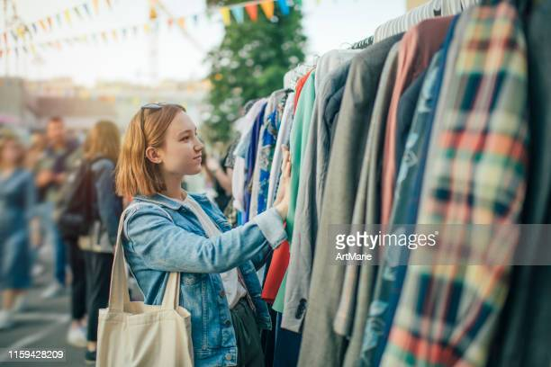 young girl choosing clothes in a second hand market in summer, zero waste concept - clothing stock pictures, royalty-free photos & images
