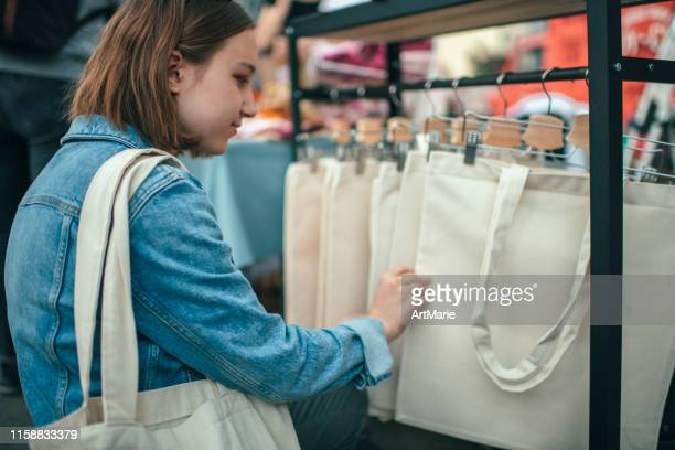 young girl choosing eco-friendly reusable cotton tote bag at an open-air market with zero waste shopping concept - tote bag stock pictures, royalty-free photos & images