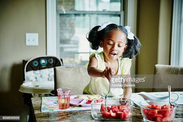 Young girl choosing fresh fruit for breakfast