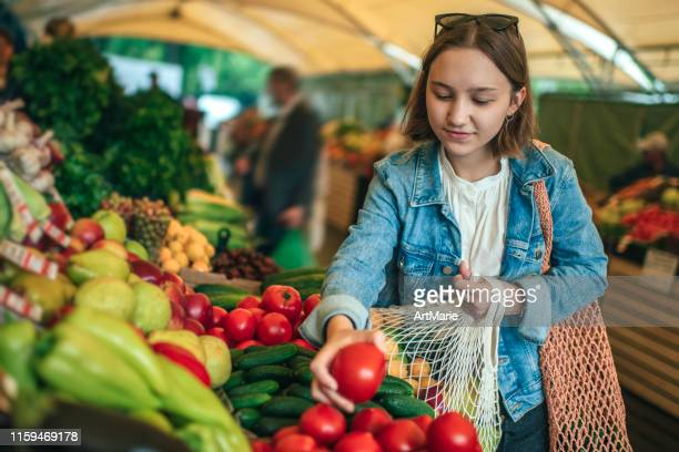 young girl choosing vegetables and fruit at a farmers market with reusable bag, plastic free and zero waste concept - reusable bag stock pictures, royalty-free photos & images