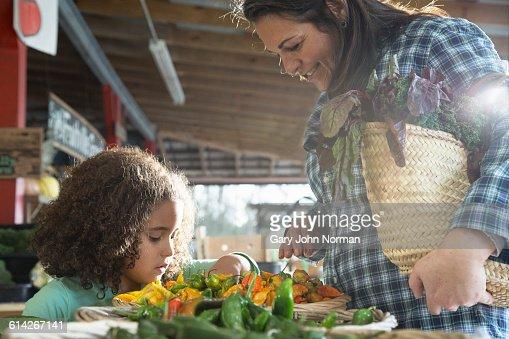 Young girl choosing vegetables in farm shop