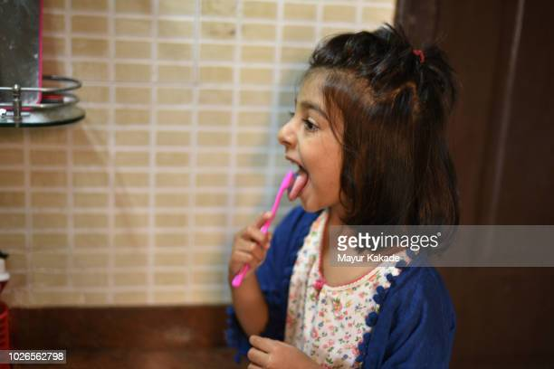 young girl cleaning her tongue - tongue stock pictures, royalty-free photos & images