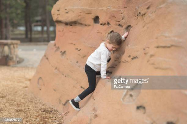 Young girl climbing a rock feature at a playground