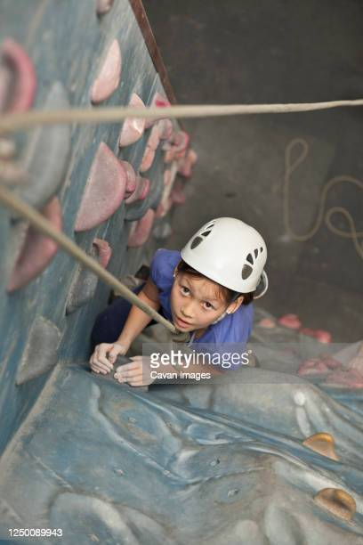 young girl climbing at indoor climbing wall in england / uk - individual event stock pictures, royalty-free photos & images