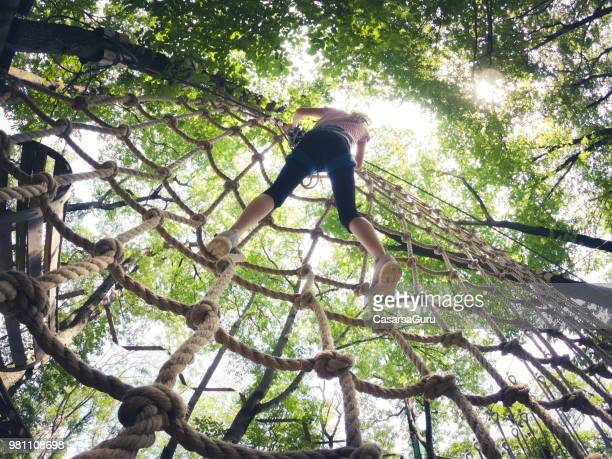 young girl climbing on rope netting in fun park - netting stock pictures, royalty-free photos & images