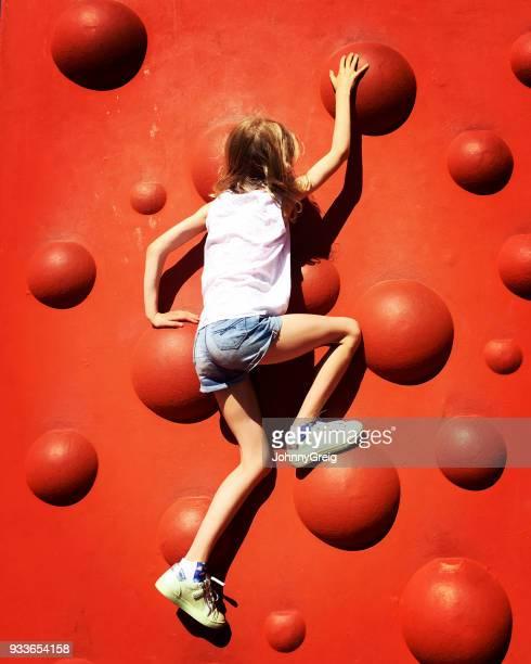 Young girl climbing red bumpy wall