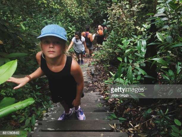 Young girl climbing steps while hiking through the rainforest of Borneo
