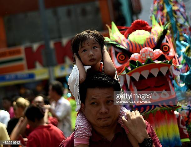 A young girl closes her ears at the sound of fireworks after dancers performed a traditional Chinese dragon dance on a street of Chinatown in Kuala...