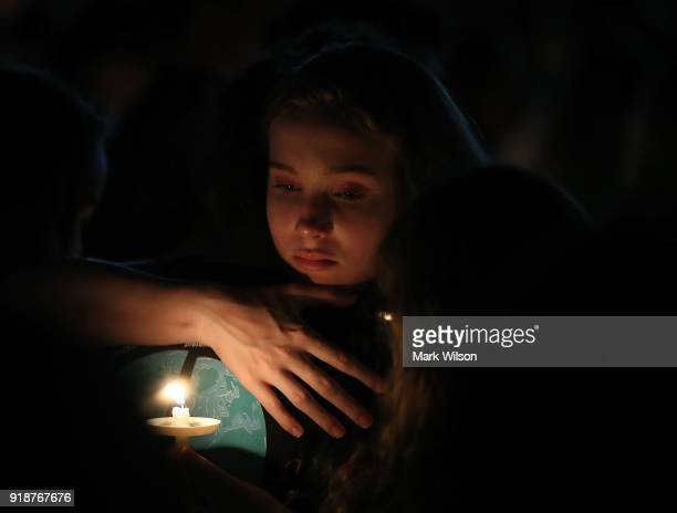 A young girl clutches a friend during candlelight vigil for victims of the mass shooting at Marjory Stoneman Douglas High School yesterday at Pine...