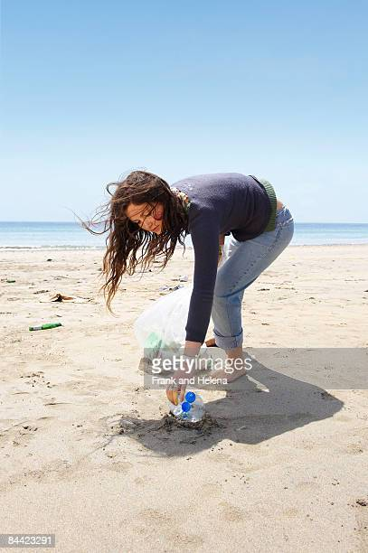 young girl collecting garbage on beach - sollevare foto e immagini stock