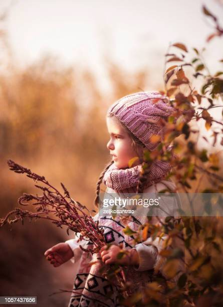 Young Girl collecting  wild flowers outdoors