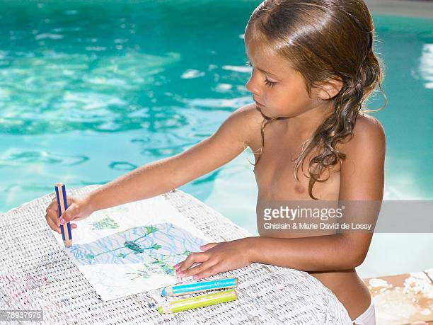 young girl coloring by a pool. - saint ferme stock photos and pictures