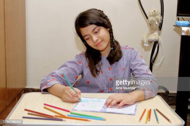 a young girl coloring the book with color pencils at home. - pakistan stock pictures, royalty-free photos & images