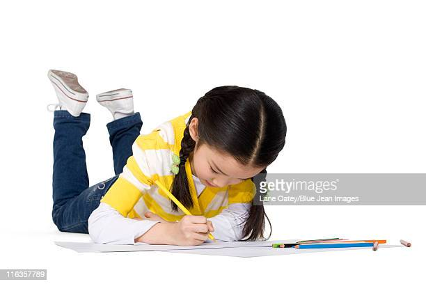 A young girl coloring while lying on the floor