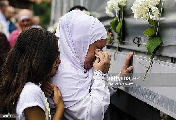 A young girl comforts a Bosnian muslim woman crying as she touches a truck carrying 136 coffins of newly identified victims of the 1995 Srebrenica...