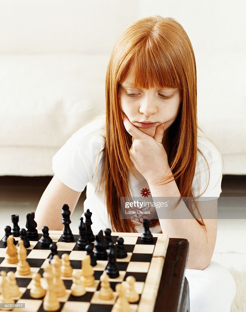 Young Girl Concentrating on a Chess Board : Stock Photo