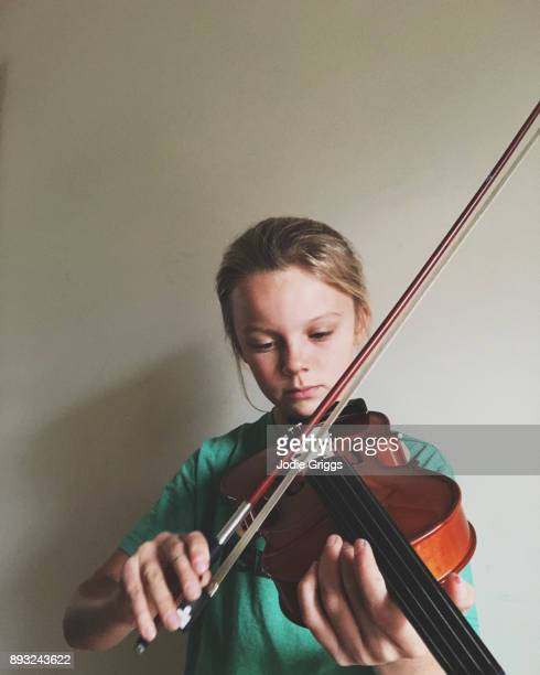Young girl concentrating while practicing the violin at home