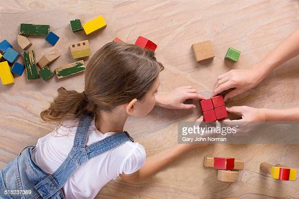 Young girl connecting wooden bricks