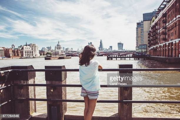 young girl contemplating river Thames, london