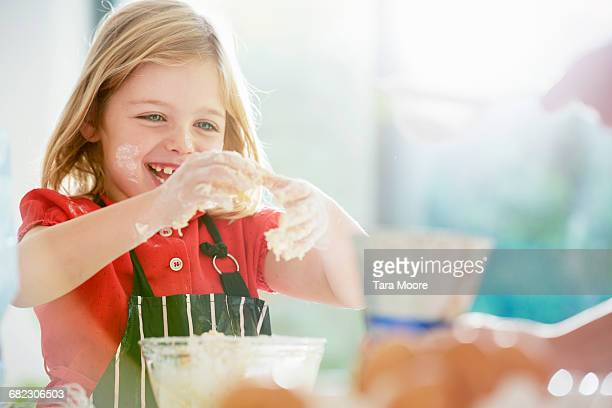 young girl cooking and getting messy