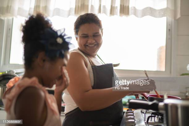 young girl cooking with her mother - single mother stock pictures, royalty-free photos & images