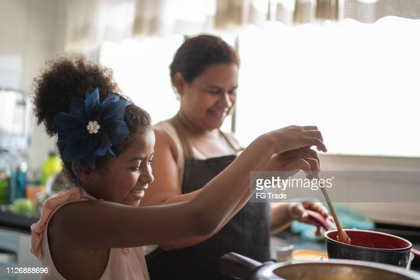 young girl cooking with her mother - black mothers day stock pictures, royalty-free photos & images