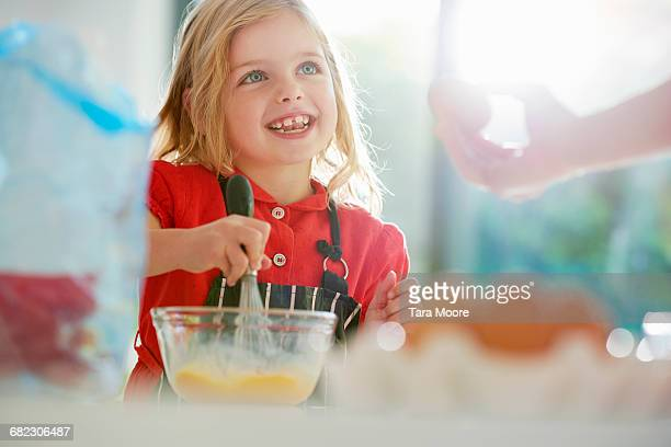 young girl cooking with mother in kitchen