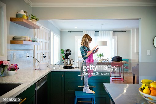 Young girl cooks in kitchen with recipe on tablet