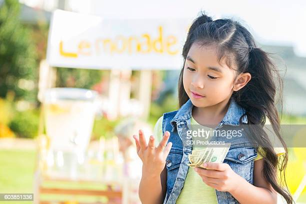 young girl counts money made from lemonade stand - counting stock pictures, royalty-free photos & images