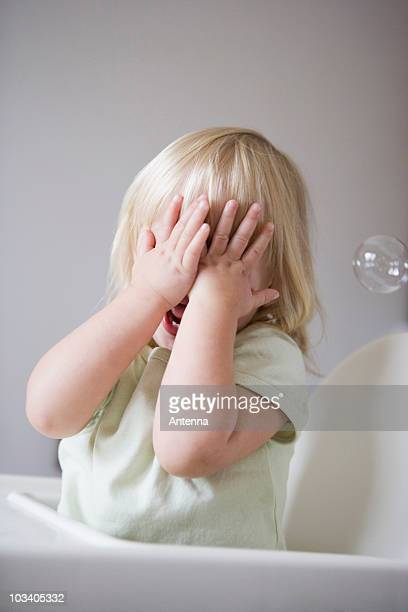 A young girl covering her face with her hands